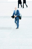 Businessman carrying briefcase crossing public square