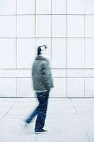 Man walking with hands in pockets on sidewalk
