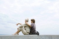Grandmother and grandson sitting together on low wall outdoors, looking at view