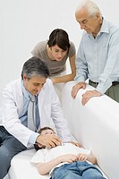 Doctor listening to young patient´s heart, family watching