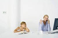 Woman sitting in front of computer, using cell phone and landline phone, daughter sulking nearby