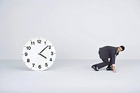 Businessman racing against time, looking over shoulder at large clock