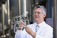 Lab technician holding model