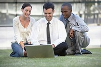 Financial advisors using a laptop on the grass