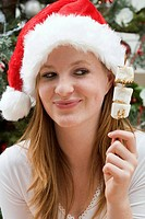 Woman in Father Christmas hat holding marshmallows on stick