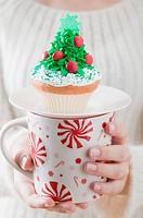 Woman holding cupcake on large mug Christmas