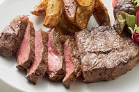 Beef steak with potato wedges and salad
