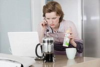 young woman at morning talking on telephone holding baby bottle and working with computer