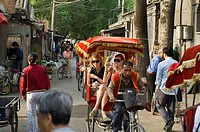 Tourists Ride by rickshaw in Hutong area near the Drum Tower, Beijing, China