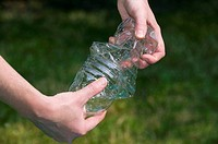 Woman´s hands crushing a plastic bottle