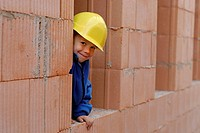 Little boy wearing a yellow hard hat smiling at a house construction