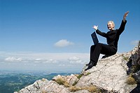Businesswoman on a mountain peak with a laptop