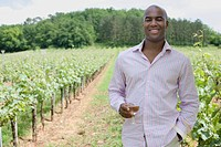 African man with wineglass in vineyard