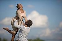 Mixed race man playfully lifting girlfriend