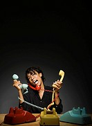 Frustrated mixed race businesswoman holding old_fashioned telephones