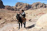Bedouin boy riding a donkey or ass (Equus asinus), Petra, Jordan, Middle East, Asia