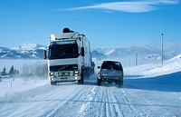 Truck and car driving along a snow-covered circular road near Hoefn, southern coast of Iceland, Europe