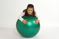Girl wearing pink dress playing with green gym ball