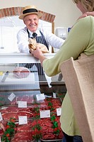 Butcher in uniform selling meat to customer