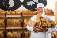 Portrait of baker in white uniform holding loaves of bread