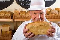 Portrait of baker in white uniform holding loaf of bread