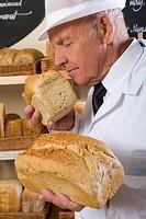 Portrait of baker in white uniform smelling loaf of bread