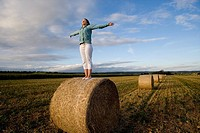 Teenage girl 16_18 standing on bale of hay in field with arms outstretched