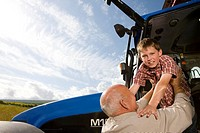 Farmer helping grandson down from tractor