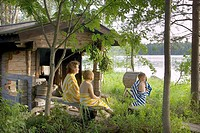 Mother and children cooling off at terrace of sauna.