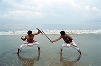 Kalaripayattu ancient martial art of Kerala showing sword and shield fighting at beach MR1