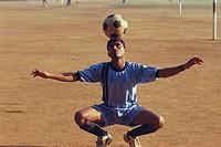 Boy balancing football on head MR672A