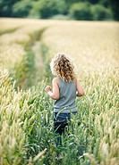 Young girl walking path in cornfield