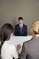 2 businesswomen interviewing man