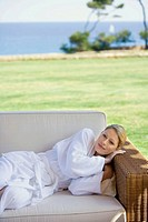 Woman in bathrobe relaxing outdoors