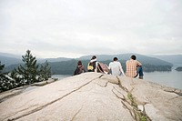 People on rock by a lake