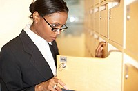 Close_up of a businesswoman opening a post locker