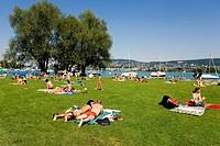 People sunbathing on a lawn on the left shore of Lake Zurich, Landiwiese, Zurich, Switzerland