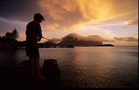 A man standing on landing stage fishing at sunset, Lord Howe Island, Australia