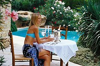 Young tourist with sparkling wine at pool, Uzes, Provence, France
