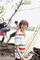 Boy holding toy sailboat near lake