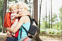 Mother and son hugging in woods