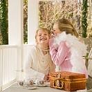 Girls having tea party on porch