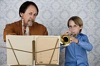 Boy playing trumpet for teacher