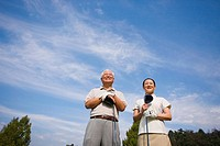 Golfers smiling against cloudy sky