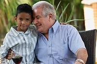 Hispanic grandfather hugging grandson