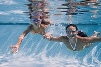 Mother and daughter swimming in swimming pool