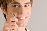 Close_up of a young man looking through a magnifying glass