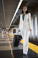 Portrait of a businesswoman pulling her luggage at a subway station