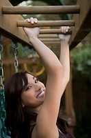 Portrait of a young woman hanging on monkey bars