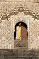 Man wearing traditional cloth looks out of a window decorated with rich ornaments Medersa Bou Inania Fes El-Bali Morocco